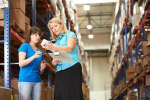 zakenvrouw en vrouwelijke werknemer in distributiecentrum foto