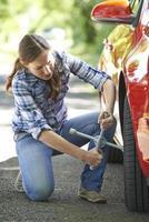 gefrustreerde vrouwelijke bestuurder met bandijzer dat wiel probeert te veranderen foto