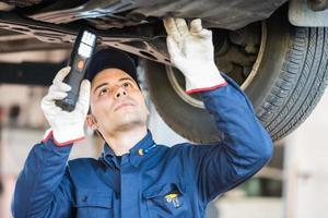 monteur die een opgeheven auto inspecteert foto