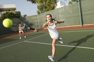 tennisser die naar bal reikt