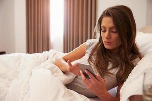 vrouw liggend in bed terwijl mobiele telefoon foto