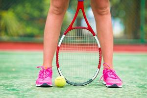 schoenen met het tennisracket en de bal op de baan