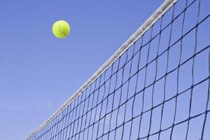 gele tennisbal vliegt over het net foto