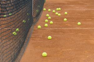 tennisballen scatered op een tennisbaan foto