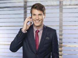 knappe, lachende zakenman aan de telefoon foto