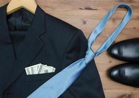 jas hanger. bind dollars en schoenen op houten lijst foto