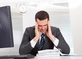 zakenman die aan hoofdpijn lijdt foto