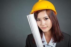 sluit omhoog Aziatisch ingenieursmeisje houdt een blauwdruk en een glimlach foto