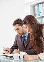 zakenman en secretaris dagboek in kantoor kijken foto