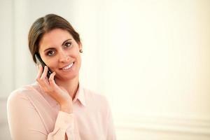 professionele jonge vrouw die op haar mobiel spreekt foto