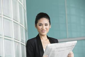 Chinese zakenvrouw lezen van de krant foto