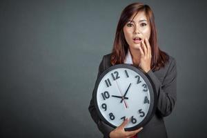 Aziatische zakenvrouw verrast houd een klok foto