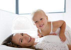 gelukkige moeder lachend met schattig klein meisje foto