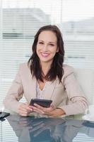 Glimlachende zakenvrouw werken op haar tablet-pc foto