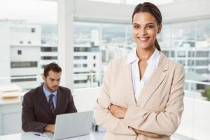 mooie zakenvrouw met gekruiste armen op kantoor foto