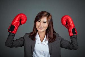 Aziatische zakenvrouw met bokshandschoen laat haar vuisten zien foto