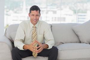 zelfverzekerde zakenman zittend op de bank foto
