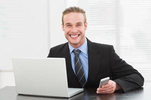 stijlvolle zakenman met behulp van laptop en mobiele telefoon foto