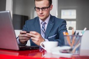jonge zakenman die in helder bureau werkt. foto