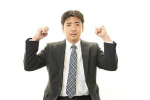 de mannelijke kantoormedewerker die vrolijk poseert foto