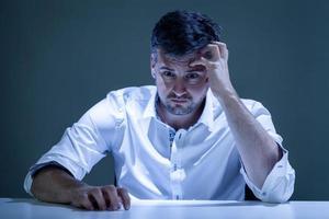 bezorgd jonge man zitten aan de tafel foto