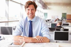 mannelijke architect zit aan zijn bureau in een kantoor foto