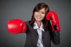 Aziatische zakenvrouw punch met bokshandschoen focus op de handschoen foto