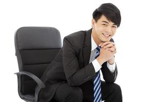 lachende jonge zakenman zittend op een stoel