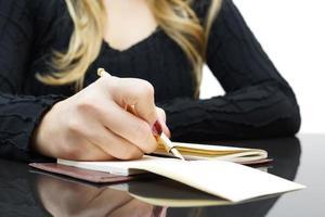 vrouw schrijft in Kladblok foto