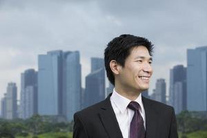 gelukkig Aziatische zakenman voor stad. foto