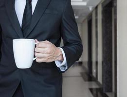 een zakenman die aan zijn bureau loopt dat een koffiekop houdt foto