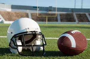 Amerikaans voetbal en helm op veld foto