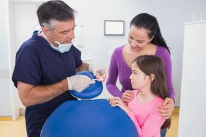 tandarts die aan jonge patiënt uitlegt foto