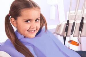 mooi klein meisje in de tandheelkundige kantoor foto