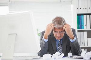 beklemtoonde zakenman met hoofd in handen foto
