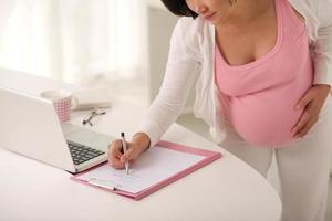 zwangere vrouw die een takenlijst schrijft voor later foto