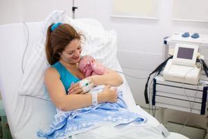 jonge moeder die een baby baart foto