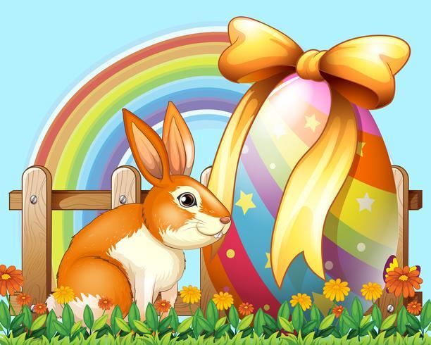 Pasen-konijn met ei in de werf vector