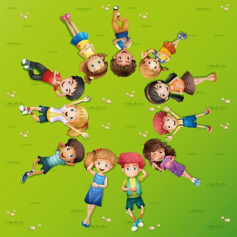 Kinderen die op gras in cirkel liggen vector