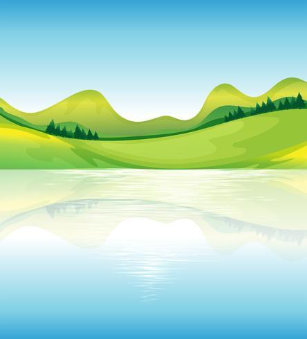 Een zicht op het water en de groene landbronnen vector