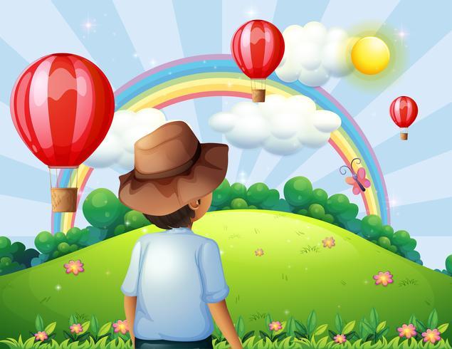 Een jongen op de heuveltop met vliegende ballonnen en een regenboog vector