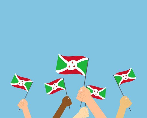Vectorillustratie die van handen de vlaggen van Burundi houden die op blauwe achtergrond worden geïsoleerd vector