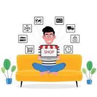 man zittend op de bank winkelt online met computer thuis