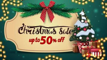 kerstuitverkoop, tot 50 korting, groene kortingsbanner met vintage frame, kerstboomtakken met rode strik, slinger en kerstboom in een pot met geschenken