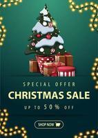 speciale aanbieding, kerstuitverkoop, tot 50 korting, verticale groene kortingsbanner met slinger, knoop en kerstboom in een pot met geschenken