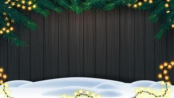 Kerstmisachtergrond, houten omheining van planken met kader van kerstboomtakken, slinger van gele bollichten en sneeuw op vloer