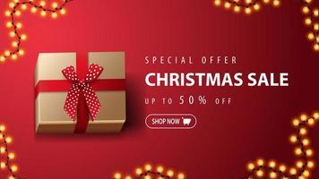 speciale aanbieding, kerstuitverkoop, tot 50 korting, rode kortingsbanner met cadeau met rode strik op rode achtergrond, bovenaanzicht vector