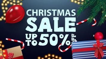 kerstuitverkoop, tot 50 korting, blauwe wenskaart met cadeautjes, rode ballon, snoepblikjes, slinger en kerstboomtakken, bovenaanzicht