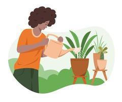 man is de planten in de tuin water geven.