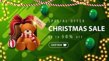 speciale aanbieding, kerstuitverkoop, tot 50 korting, prachtige groene kortingsbanner met veelhoekige textuur, slingers, groene ballonnen en cadeau met teddybeer vector